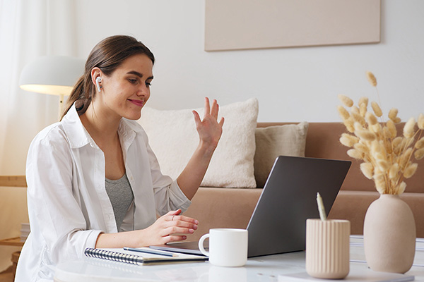 woman looking at laptop and waving